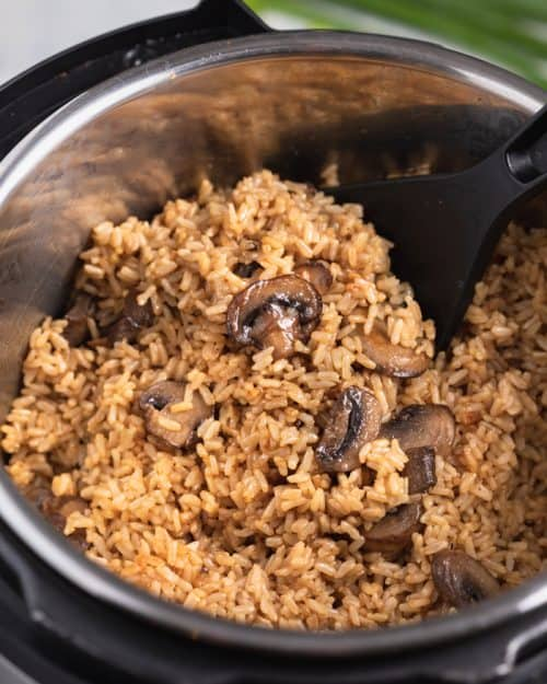 An instant pot filled with cooked brown rice and mushrooms.