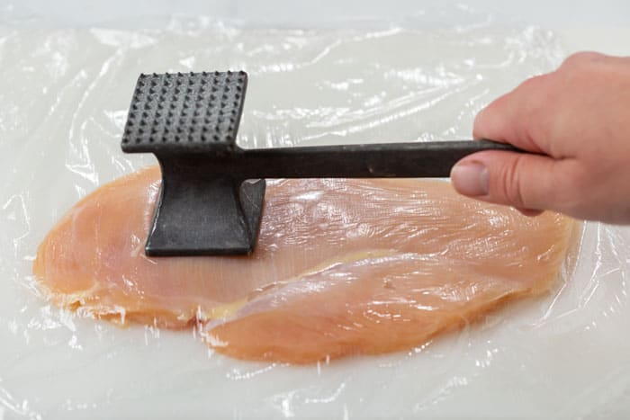 A hand holding a meat tenderizer and pounding a slice of chicken breast with saran wrap over it.