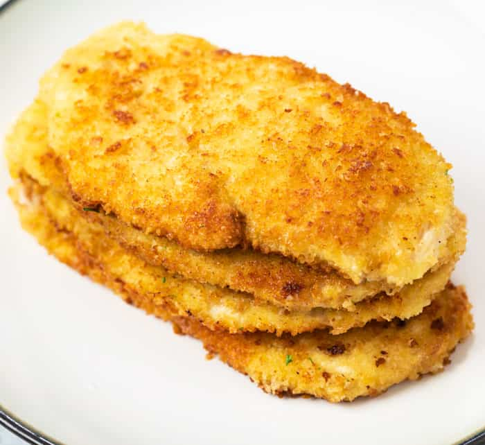 A pile of crispy golded breaded chicken on a plate for chicken milanese.