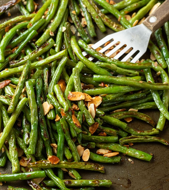 A dark roasting pant with a spatula scooping up roasted green beans topped with sliced almonds.