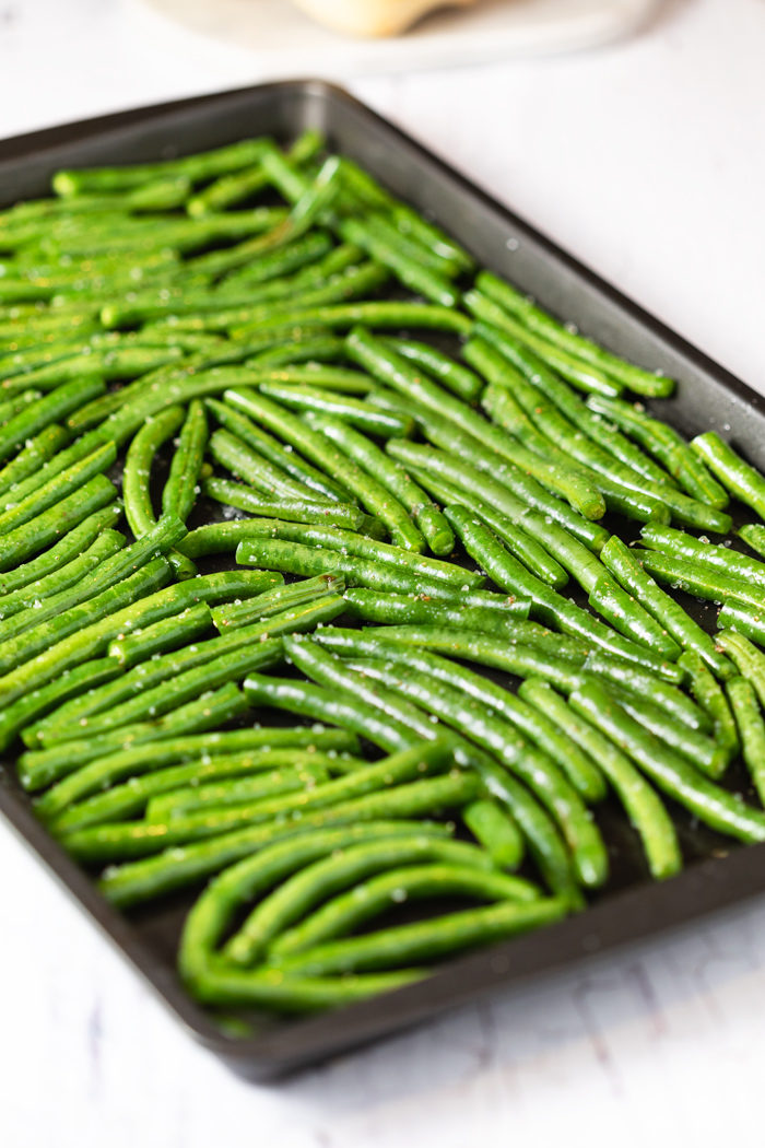Uncooked, salted green beans on a baking sheet before being roasted in the oven.