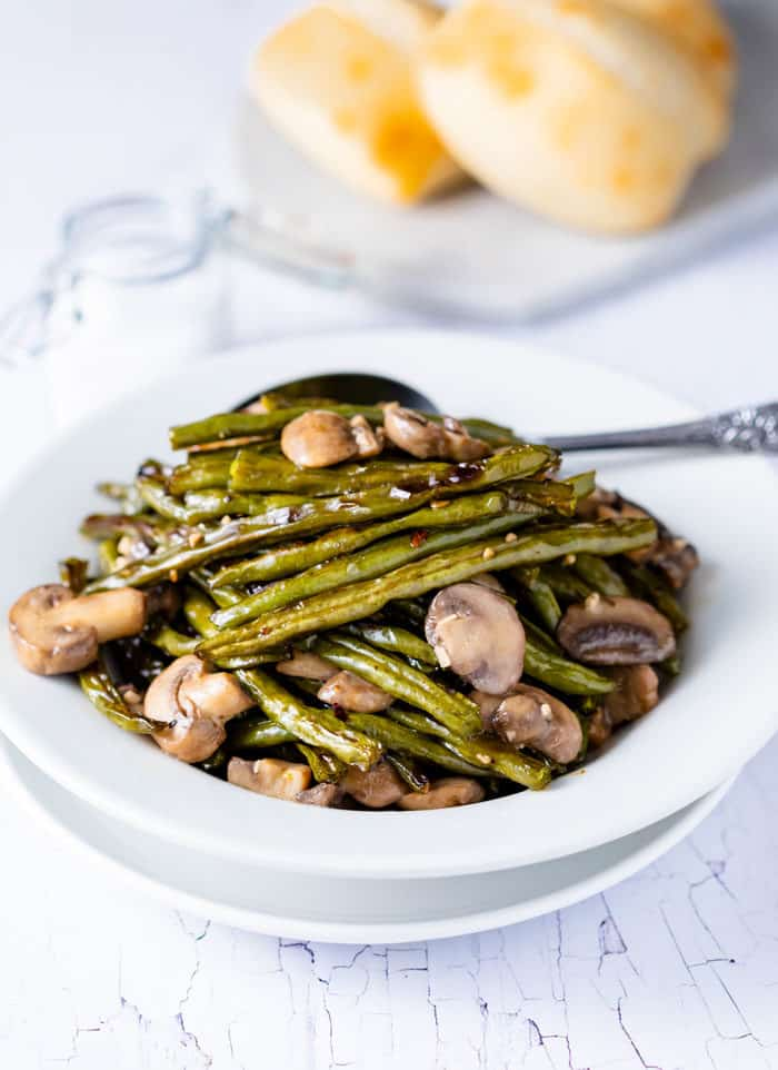 Roasted green beans and mushrooms in a white bowl on a white table with rolls in the background.