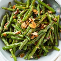 A bowl of roasted green beans topped with crispy sliced almonds.