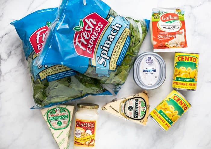 Ingredients needed to make spinach and artichoke dip recipe on a white granite countertop