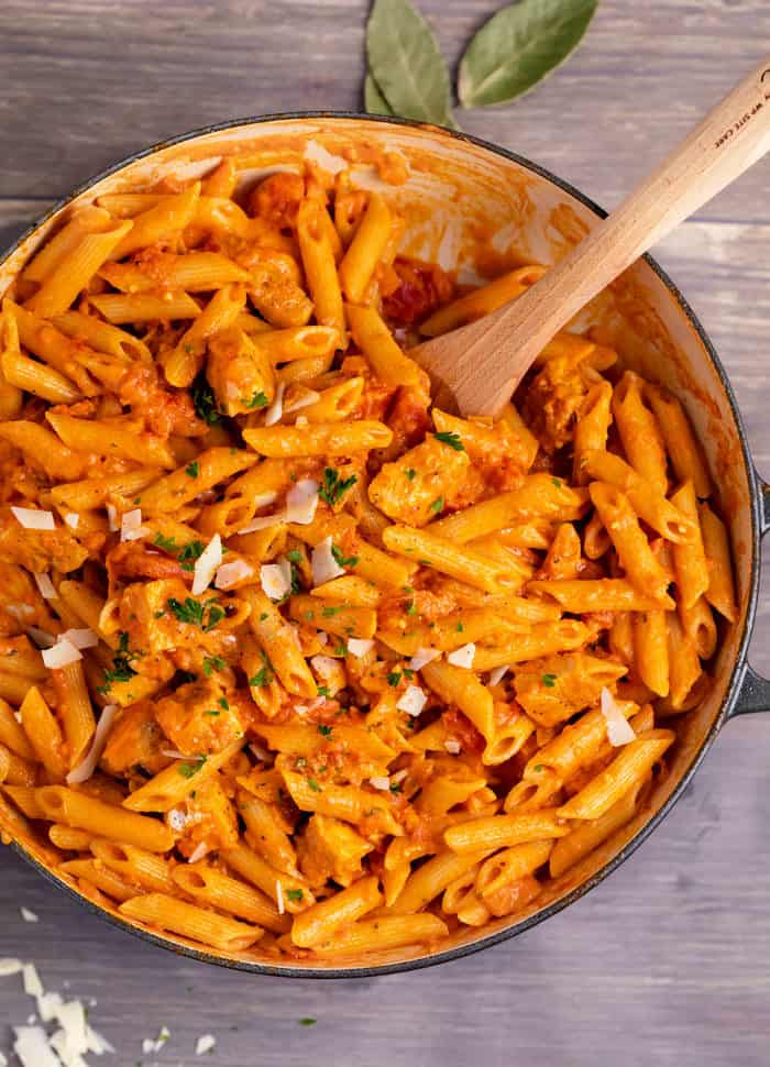 Overhead view of a large pot filled with penne alla vodka and with a wooden spoon.