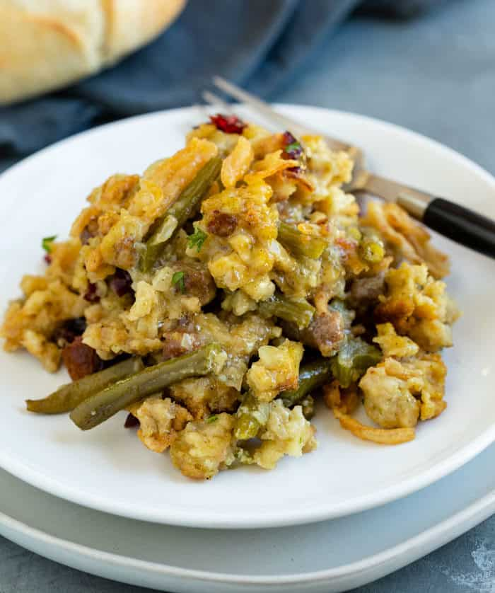 Stuffing and green bean casserole on a white plate with a fork next to it.