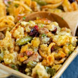 A casserole dish with a wooden spoon scooping out stuffing casserole with green beans.