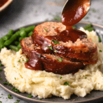 A pile of mashed potatoes with The Pioneer Woman Meatloaf with a spoon drizzling glaze on top.