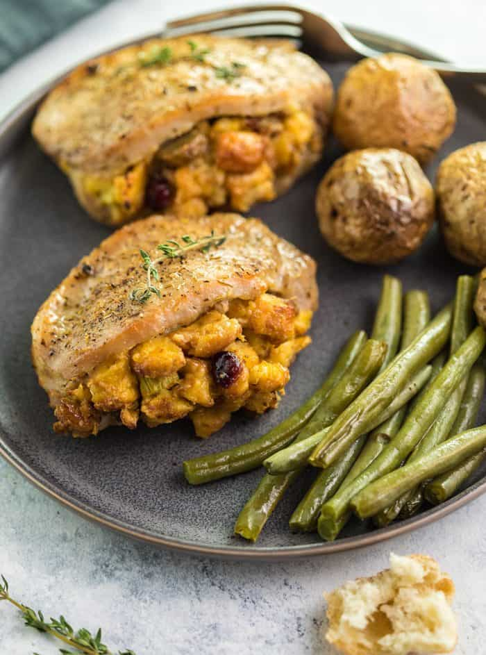 Golden brown pork chops filled with golden stuffing on a plate with green beans and roasted potatoes