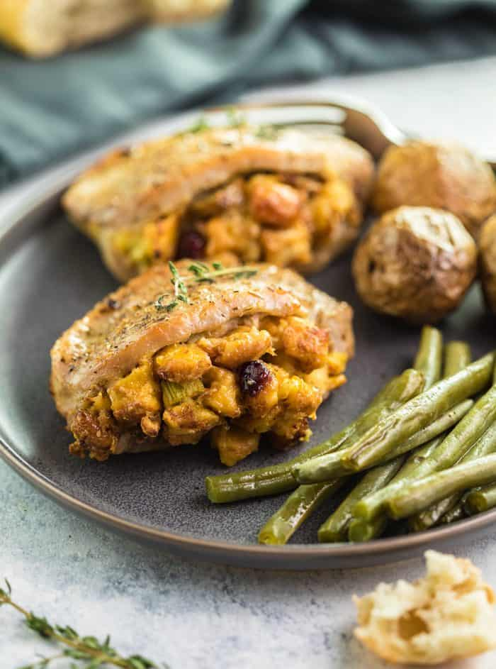 Seasoned Baked Pork Chops filled with Stuffing on a plate with green beans and roasted potatoes