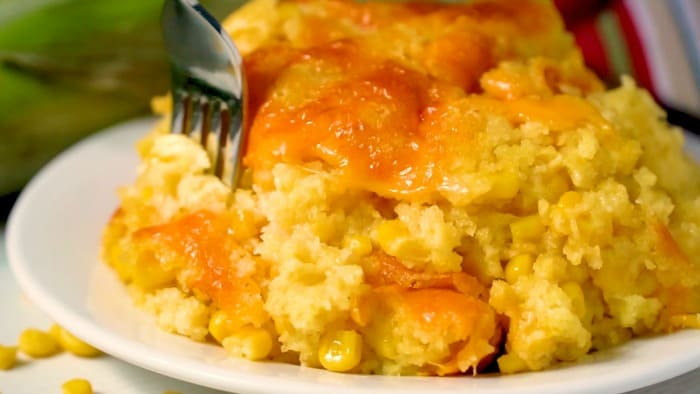 A white plate with corn casserole and a fork taking some of it.