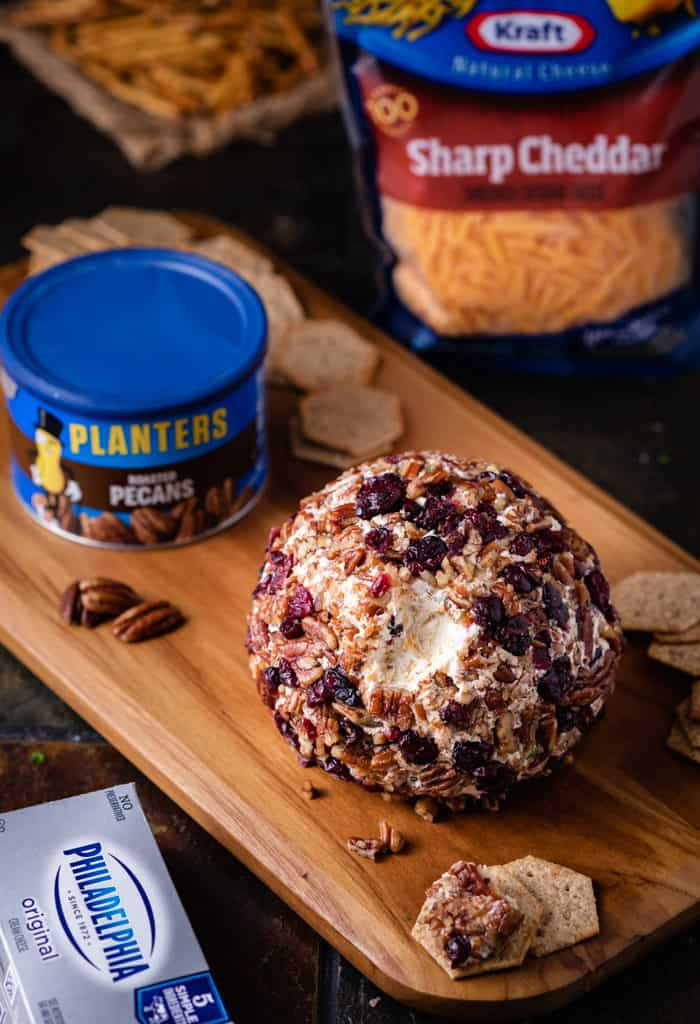 Wooden Cutting Board with Pineapple Cranberry Cheese Ball with planters pecans and grated cheese in background.
