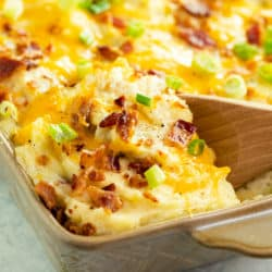 Twice baked potato casserole in a casserole dish with a wooden spoon scooping it up.