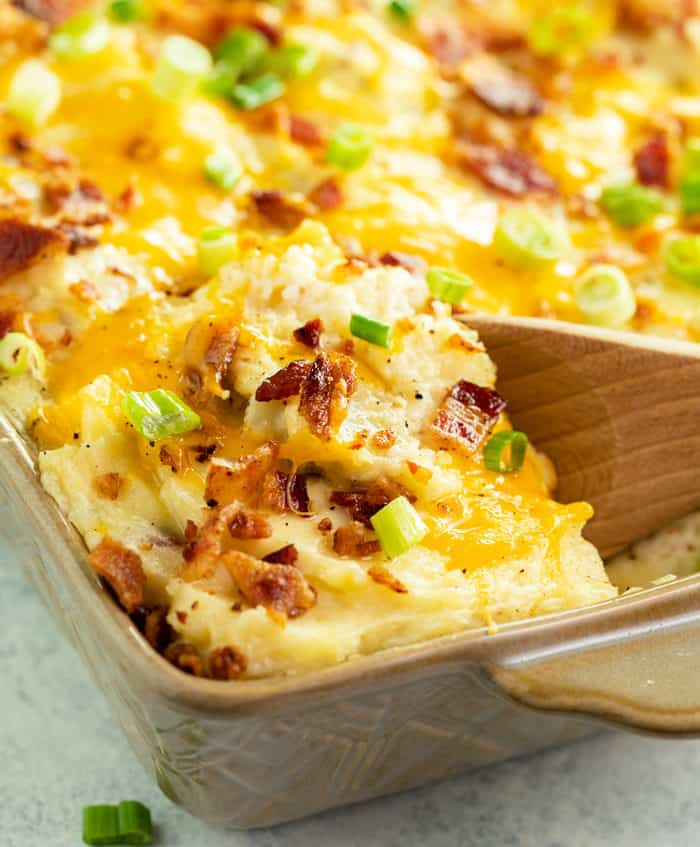 A close up image of a wooden spoon filled twice baked potato casserole in a casserole dish.