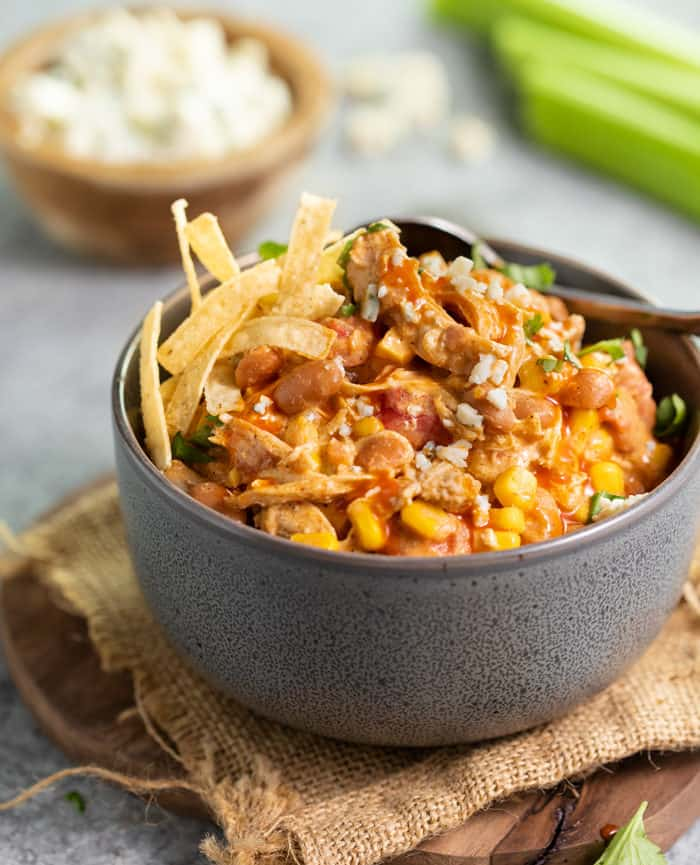 Grey bowl filled with buffalo chicken chili with crispy tortilla strips on top.