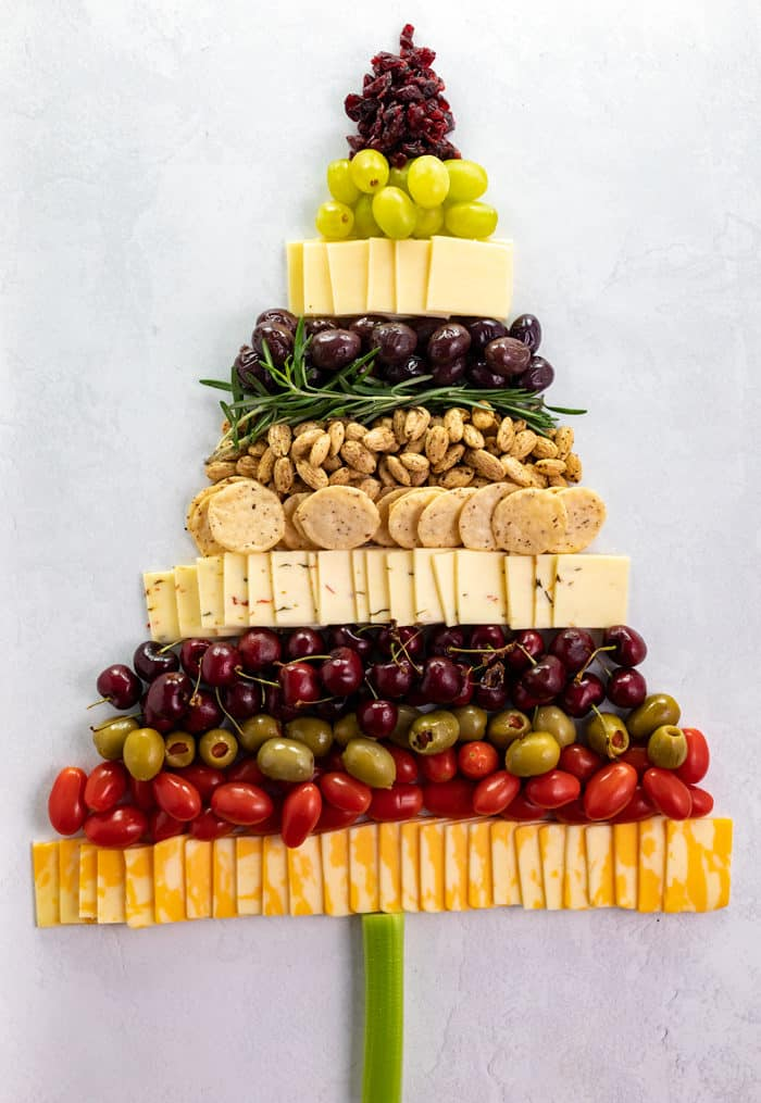 Overhead shot of cheese, crackers, almonds, olives, grapes, and tomatoes in the shape of a Christmas tree.