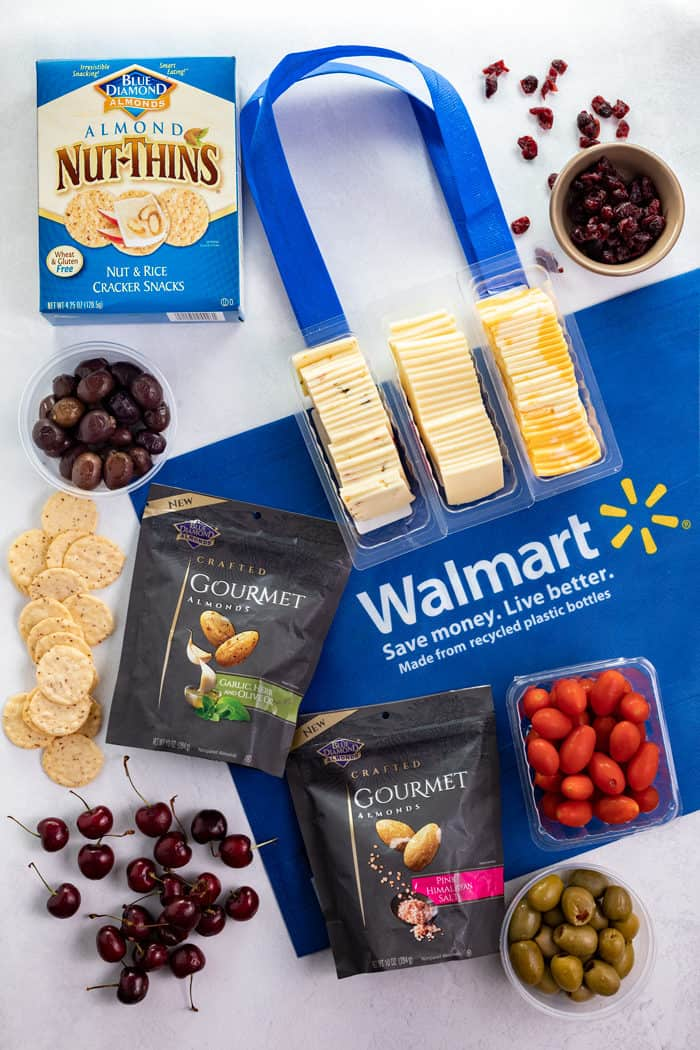 Overhead shot of Walmart bag, crackers, almonds, olives, cranberries, cherries, and tomatoes.