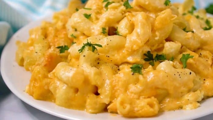 Creamy macaroni and cheese on a white plate topped with chopped parsley.