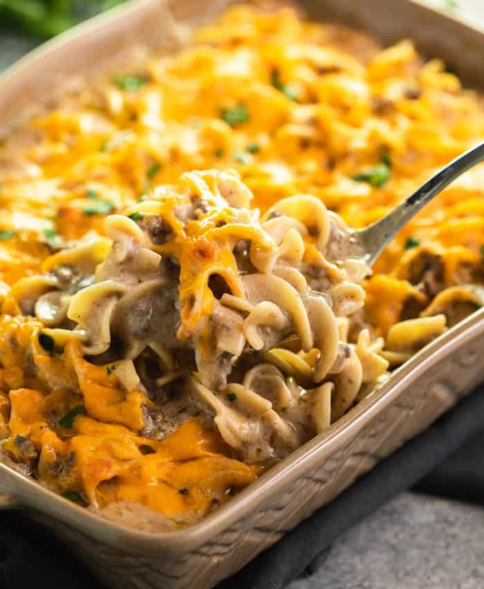 Casserole dish with a big spoon filled with cheesy ground beef stroganoff.