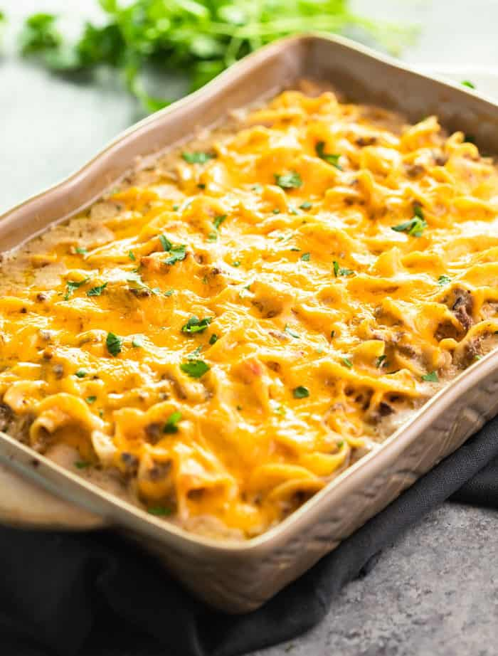 A casserole dish filled with egg noodles for ground beef stroganoff casserole topped with melted cheese.