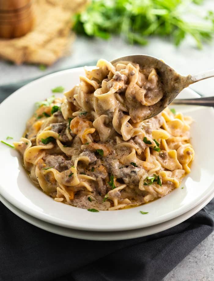 A white plate filled with egg noodles in a stroganoff sauce with ground beef, and a spoon pouring more on top of the plate.