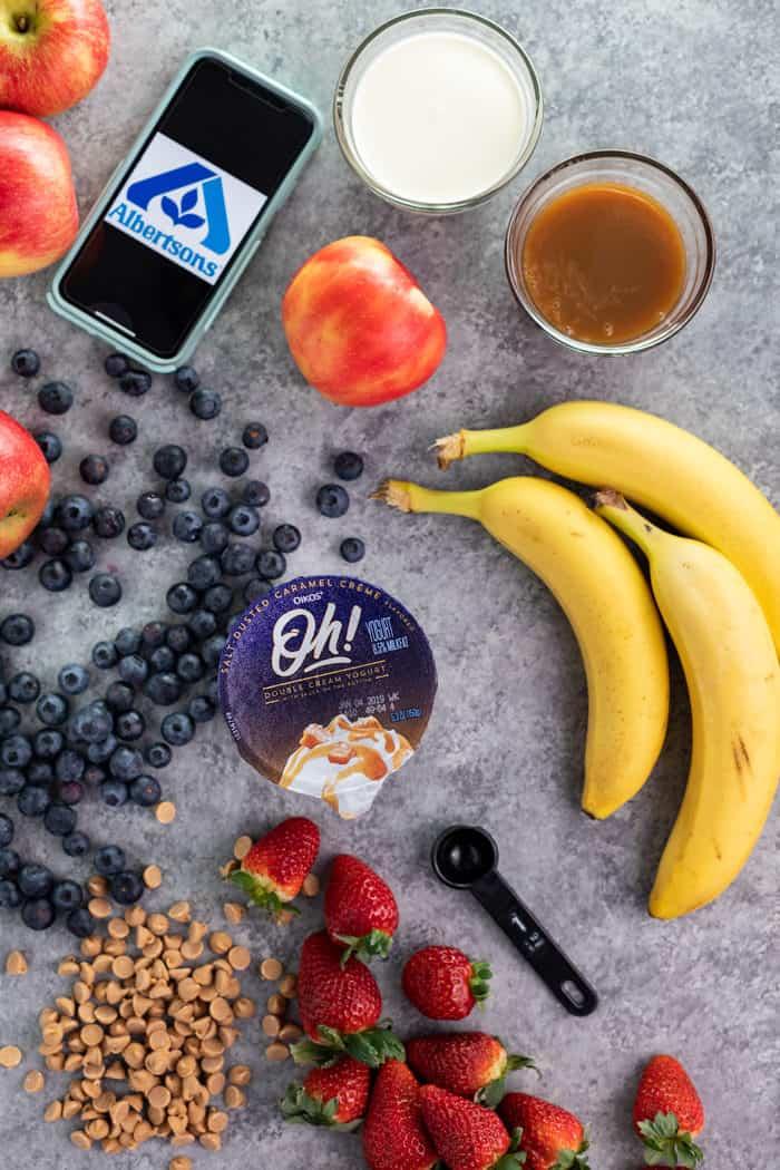 Overhead shot of blueberries, strawberries, bananas, yogurt, apples, and caramel for making fruit dip.