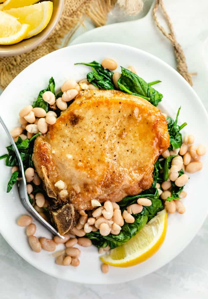 overhead shot of pan fried pork chops on a bed of sauteed spinach with white beans and a lemon wedge on a white plate.