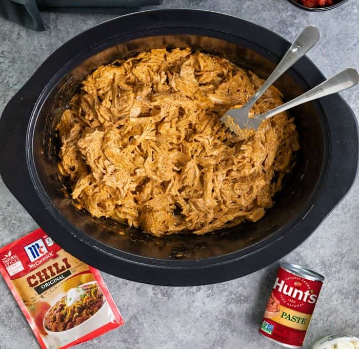 Overhead shot of shredded buffalo chicken in crock pot.