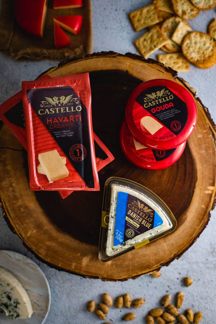overhead image of 3 Castello cheese varieties on a round wooden serving tray with crackers in background.