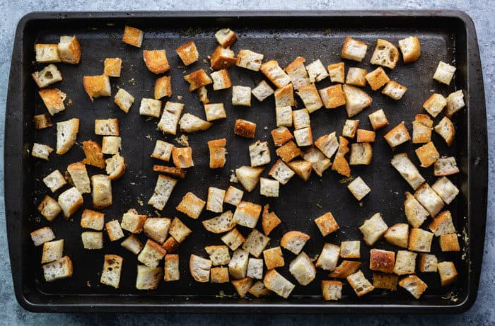 cubes of bread on a baking sheet after being baked for homemade croutons.
