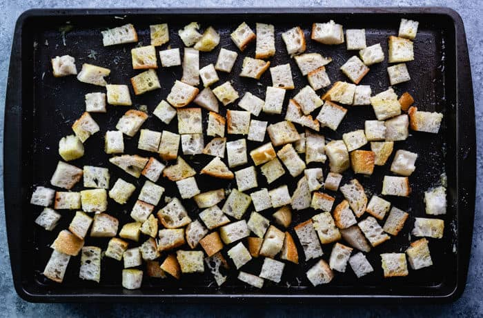 cubes of bread on a baking sheet before being baked to make homemade croutons.
