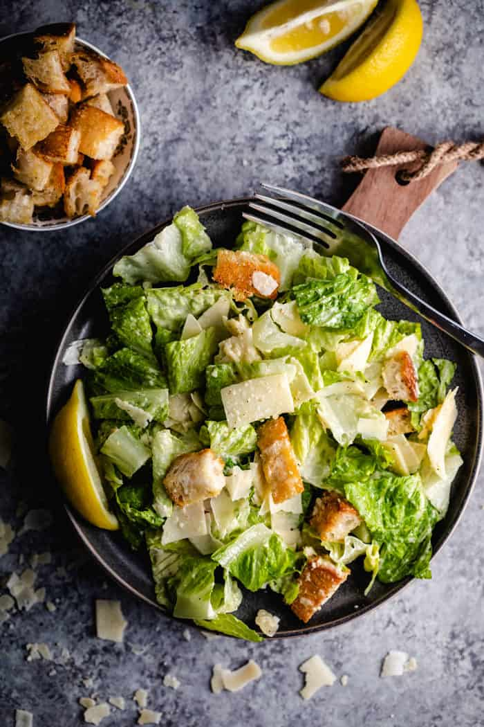 A plate with chicken caesar salad topped with croutons and Parmesan cheese.