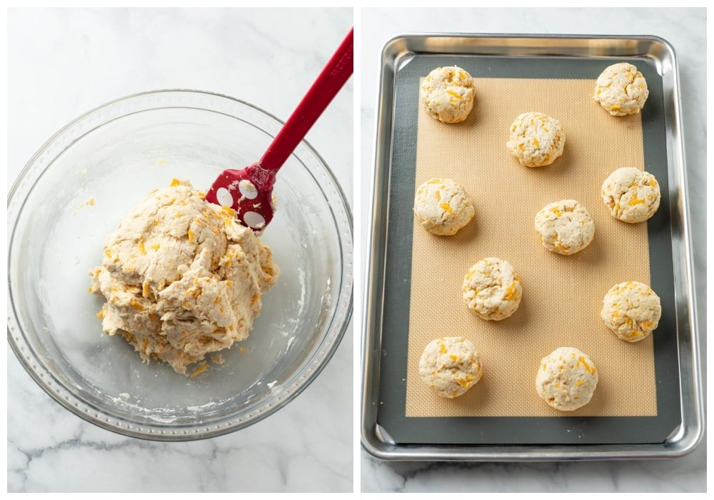 A bowl of cheddar bay biscuit dough next to a baking sheet of unbaked biscuits.