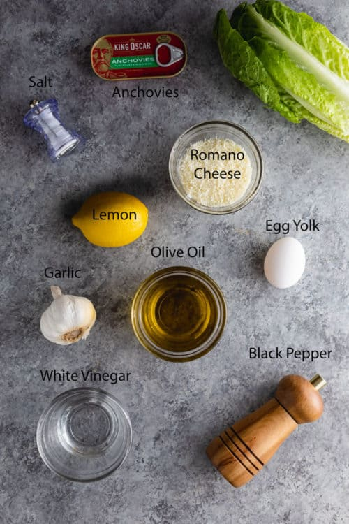 Ingredients needed to make homemade caesar dressing on a blue table.