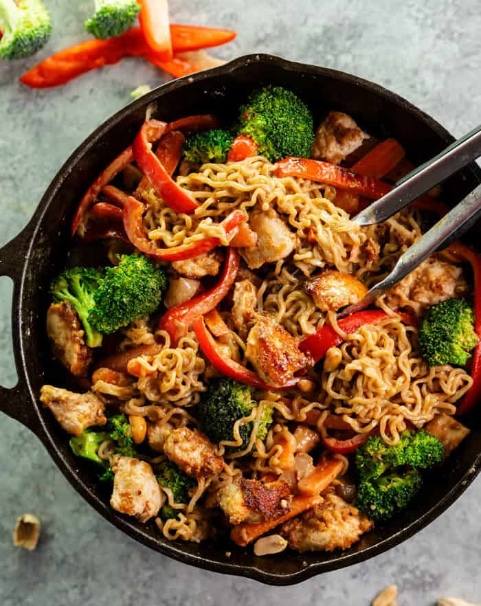 Overhead view of a cast iron skillet with ramen noodle stir fry with chicken and broccoli.