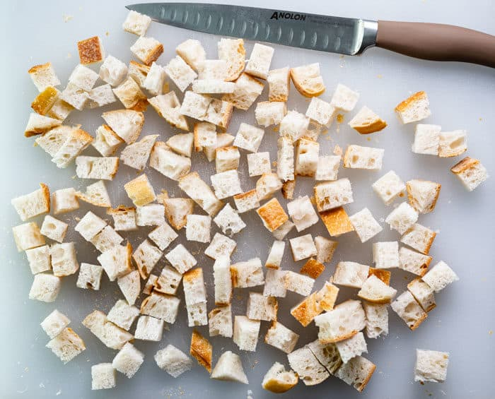 bread on a cutting board cut into cubes for homemade croutons.