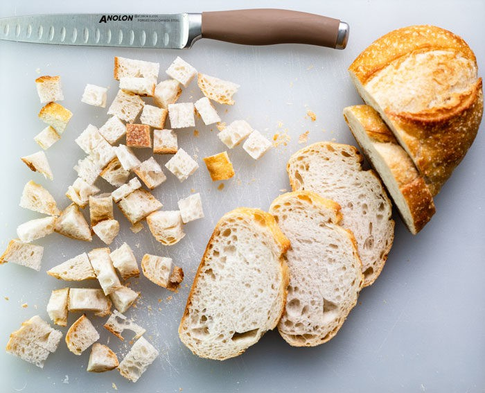 loaf of sourdough bread on a white cutting board with a knife that's partially cubed and sliced for homemade croutons.