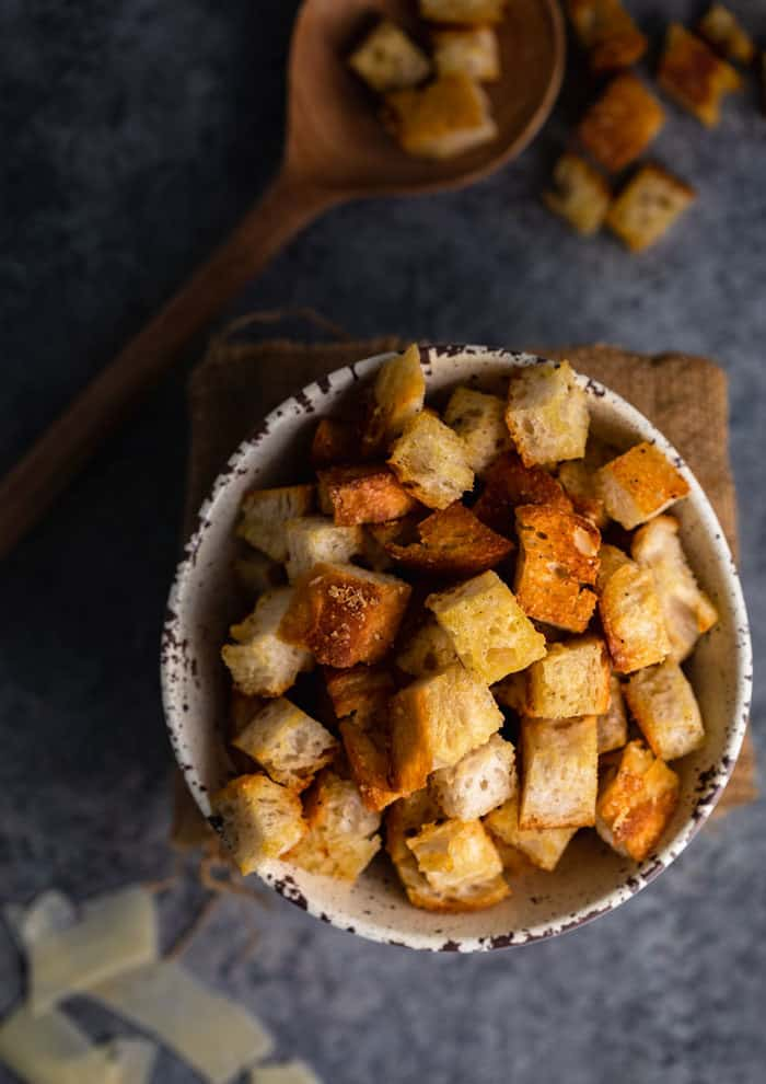 homemade croutons in a bowl on a shadowy table with a wooden spoon holding croutons on the background.