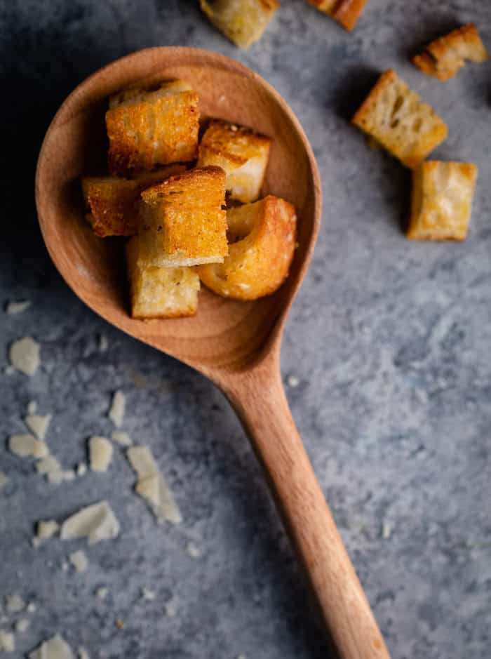 wooden spoon holding homemade croutons on a shadowy surface sprinkled with grated Parmesan.