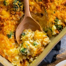 broccoli chicken rice casserole in a casserole dish with a wooden spoon in it.