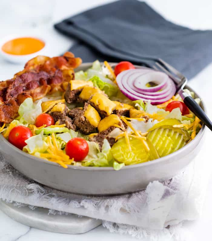A big gray bowl filled with cheeseburger salad with big mac sauce and a dish towel in the background.