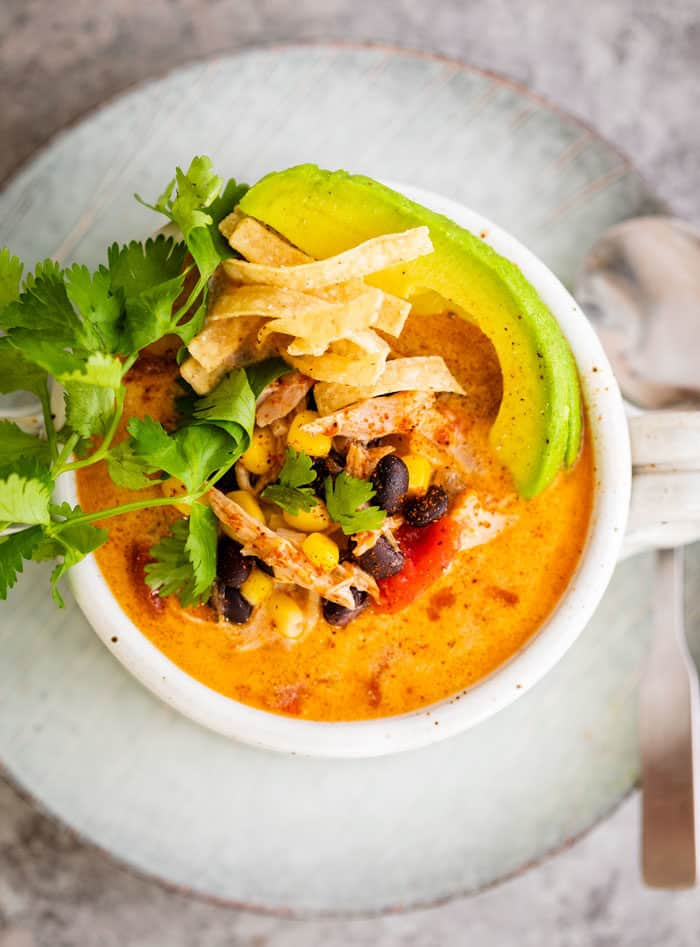 Birds Eye view of creamy chicken tortilla soup garnished with fresh cilantro and sliced avocado in a soup crock.