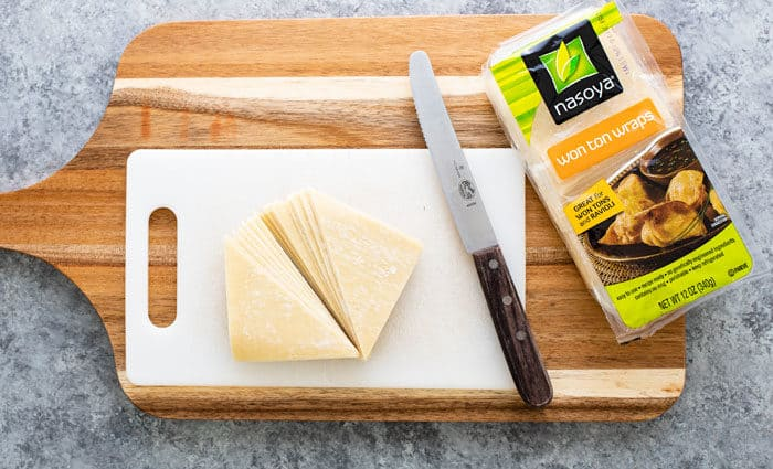 wonton wraps on a wooden cutting board next to the package.