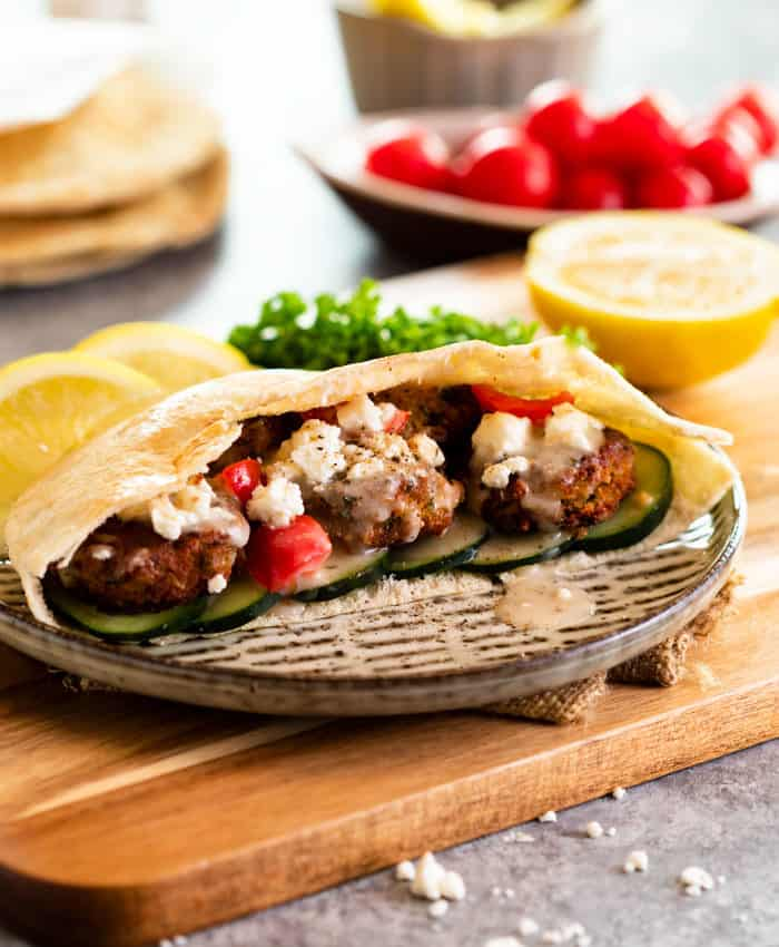 A falafel pita wrap on a wooden cutting board with lemon wedges and parsley.