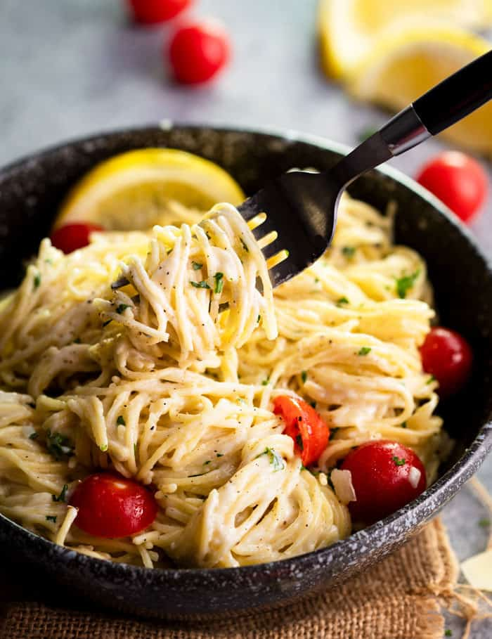A black bowl filled with Parmesan Garlic Pasta with a fork lifting up the noodles.