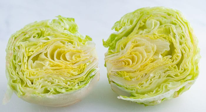 a head of iceberg lettuce cut in half.