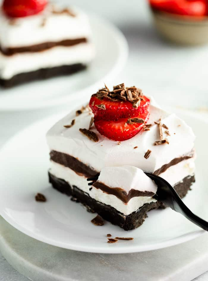 A fork digging into a slice of Oreo dessert with a strawberry on top.