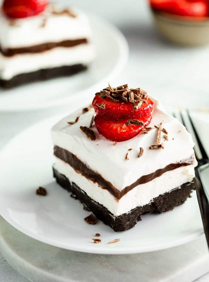 4 layered Oreo delight with a strawberry on top and chocolate shavings on a white plate.