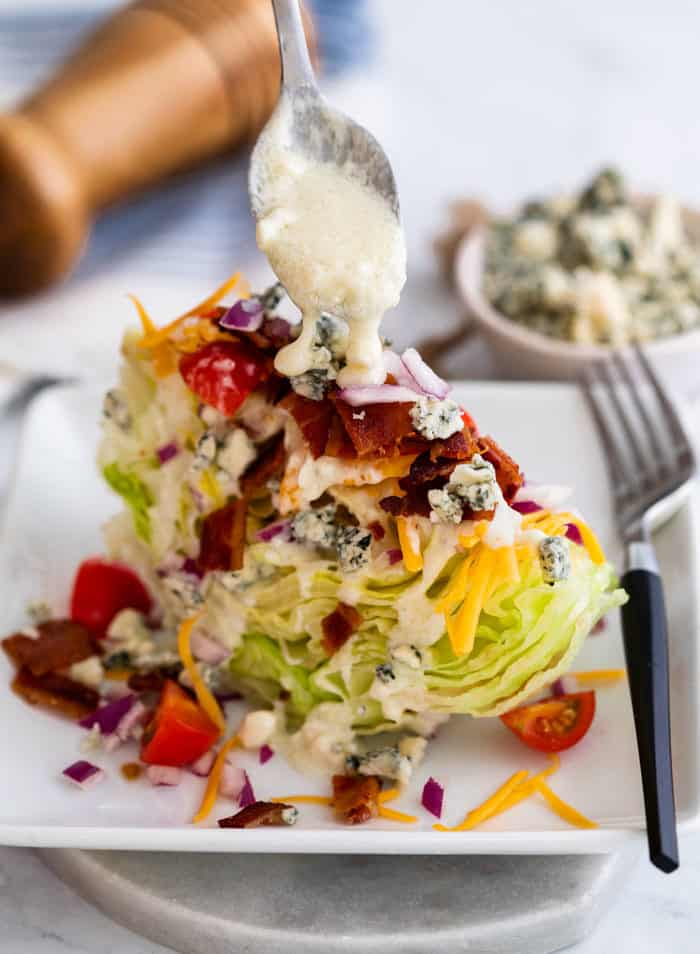a spoon drizzling blue cheese on top of a wedge salad on a white plate.