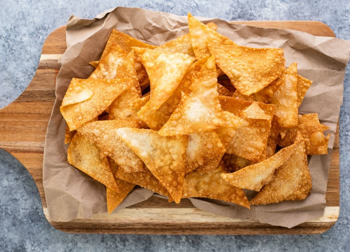 Golden fried wonton chips on a wooden cutting board after being fried.